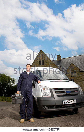 Handyman in coveralls holding toolbox and leaning on work van - Stock Image