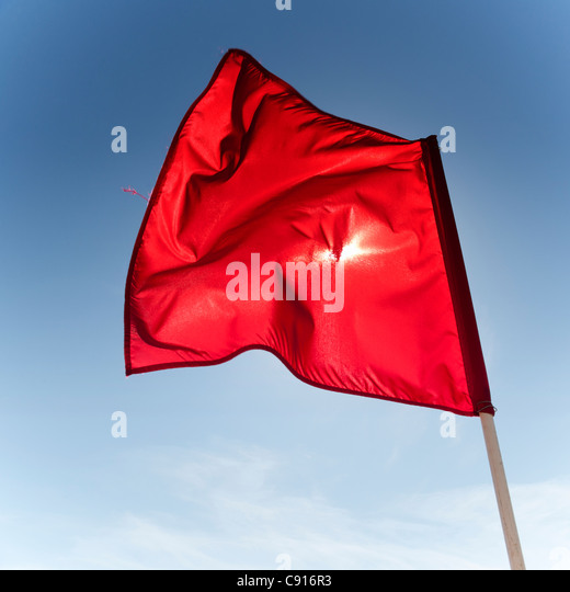 The red flags at Coney Island denote that it is not safe to swim in the sea due to strong currents that pose a dangerous - Stock Image