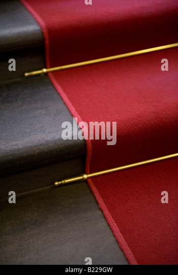 Red carpet, brass stair rods and staircase - Stock Image