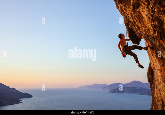Rock climber resting while climbing overhanging cliff - Stock Image