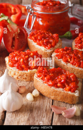 Selective focus on the ajvar on whole grain bread closeup on the table. Vertical - Stock Image