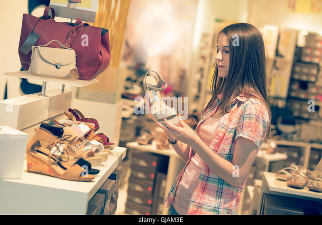 Young woman chooses shoes at a store. Toned photo - Stock Image