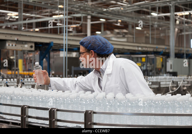 Factory worker examining bottled water - Stock Image