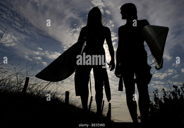Young couple prepare to go surfing - Stock Image