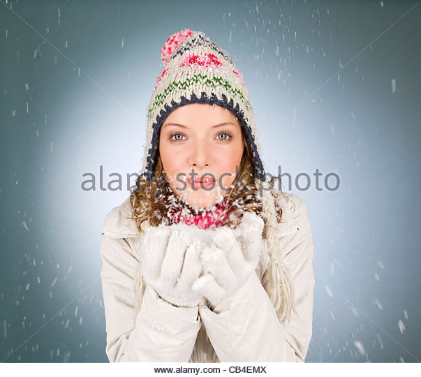 A young woman blowing a handful of snowflakes - Stock Image