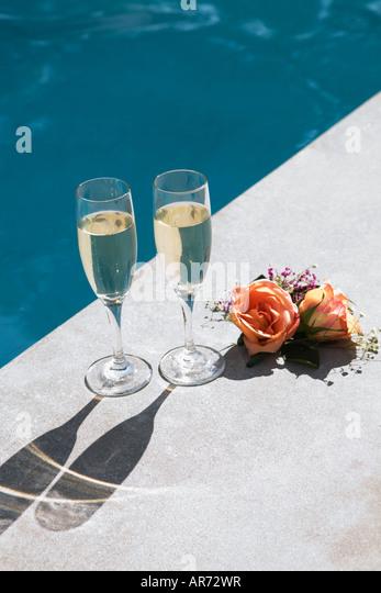 Champagne glasses beside swimming pool - Stock-Bilder