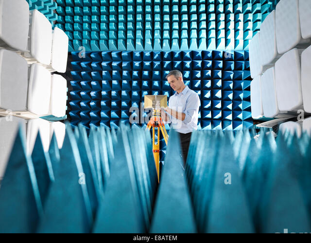 Male scientist preparing to measure electromagnetic waves in anechoic chamber - Stock-Bilder