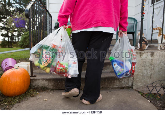 A woman brings food donated to her from a food bank back to her home. - Stock Image