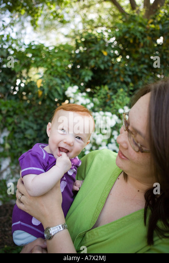 Red haired baby girl smiles at camera outdoors, being held by mother - Stock Image