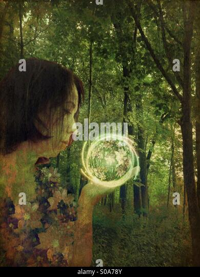 Woman in the woods holding a floral orb - Stock Image