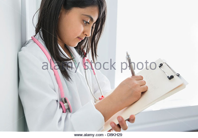 Girl pretending to be doctor at home - Stock Image
