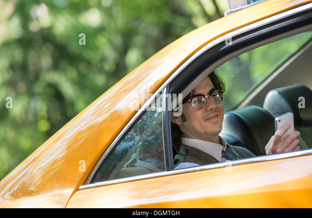 City life. People on the move. A young man in the back seat of a taxi. - Stock Image