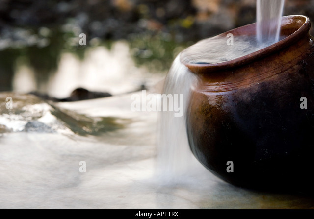 Filling an Indian Clay pot with fresh clean water at a hand water pump in the indian countryside. Andhra Pradesh, - Stock Image