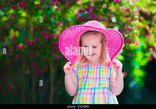 Little cute girl with flowers. Child wearing a pink hat playing in a blooming summer garden. Kids gardening. Children - Stock Image