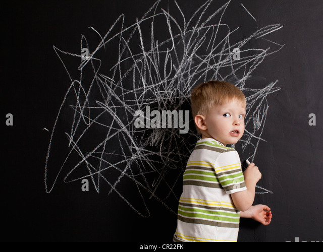 Cute toddler boy (2-3) standing against blackboard with daub written in chalk - Stock Image