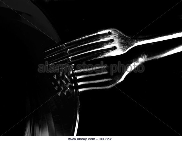 Plate and fork on black - Stock Image