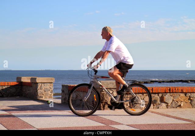 Uruguay Montevideo Rambla O'Higgins Hispanic man bicycle bike riding Rio de la Plata Atlantic Ocean Playa del - Stock Image