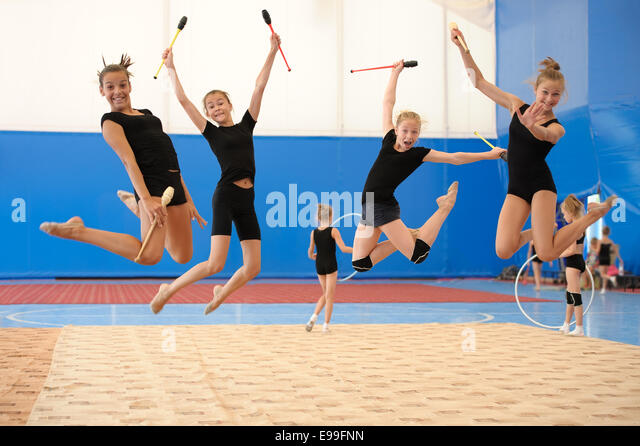 Girls with Indian clubs during high jump - Stock Image