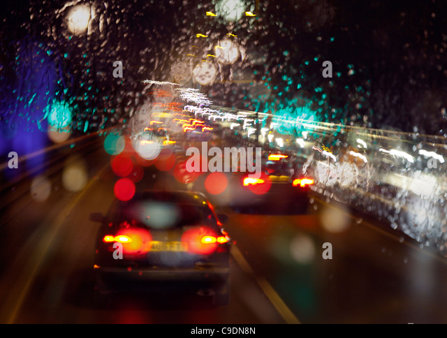 Late night wet rain on windscreen poor visibility while driving out of London in evening rush hour in heavy traffic - Stock Image