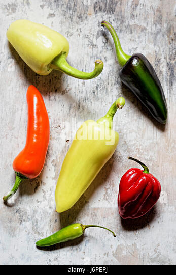 Green, red, yellow and orange peppers on white background - Stock Image