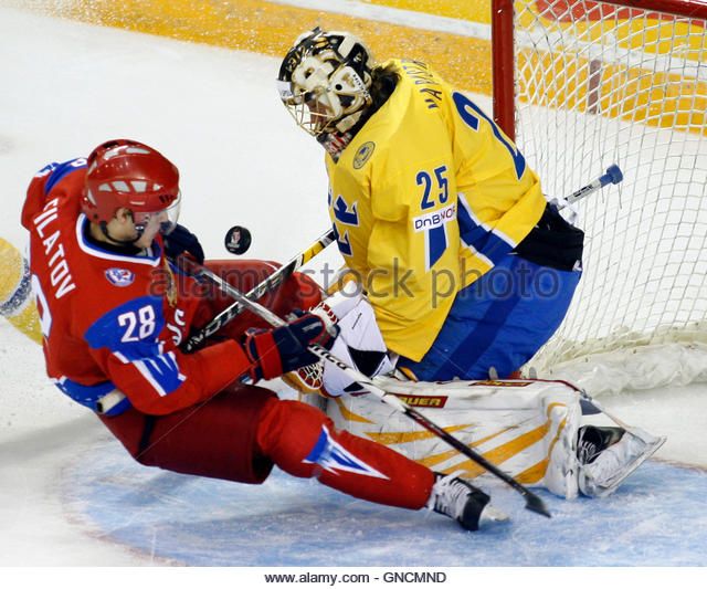 Russia's captain Nikita Filatov (L) slides into Sweden's goalie Jacob Markstrom on a scoring attempt during - Stock Image