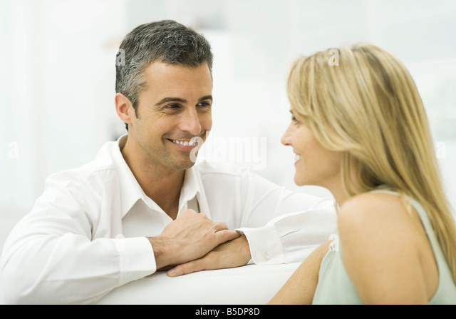 Couple smiling at each other, man leaning against armrest with arms folded - Stock-Bilder