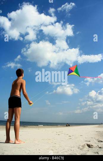 A teen boy flying his kite at a beach - Stock Image