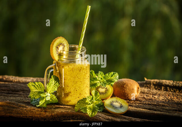 Healthy green smoothie made of kiwi on a bark - Stock Image
