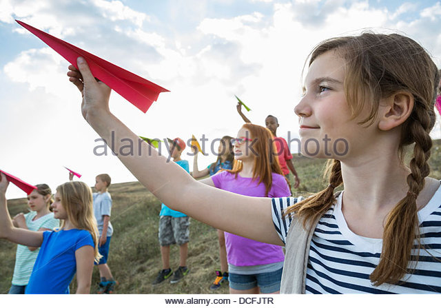 Girl holding red paper airplane outdoors - Stock Image