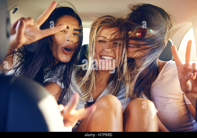 Three beautiful female friends make peace signs while seated in back seat of car with wind in their hair - Stock Image