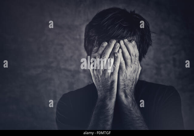 Grief, man covering face and crying, monochromatic image - Stock Image