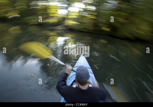Man Canoeing in Whirling Motion - Stock Image