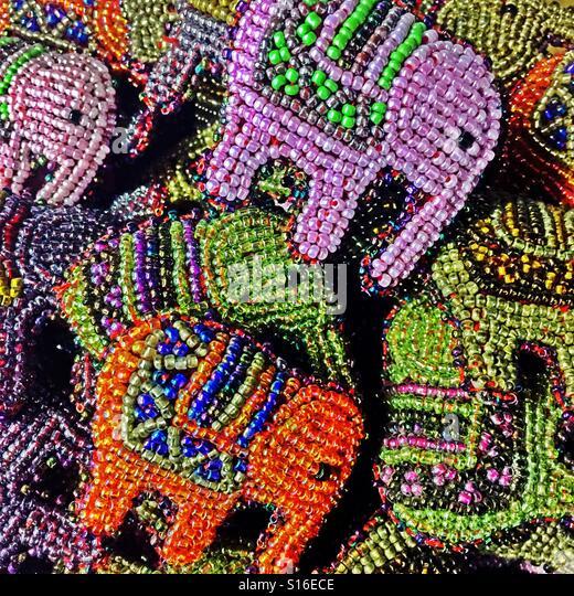 Colorful beaded elephant pins in sales display. - Stock-Bilder