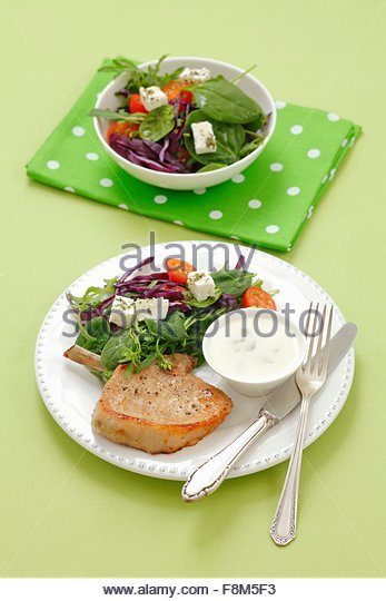 A pork chop with a vegetable salad, feta cheese and a yogurt dip - Stock Image