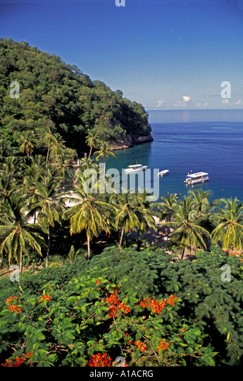 St Lucia lush foliage rain forest boats water clouds - Stock Image