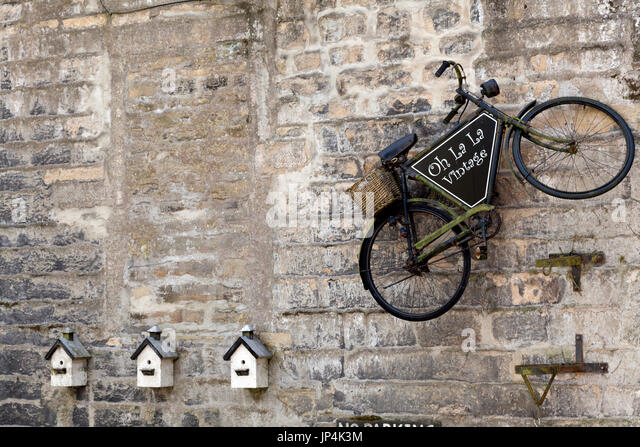 Old bicycle on the wall of Oh La La vintage shop, Haworth, West Yorkshire - Stock Image