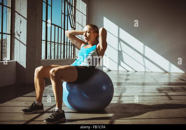 Young woman in gym sitting on exercise ball hands behind head, looking away - Stock-Bilder