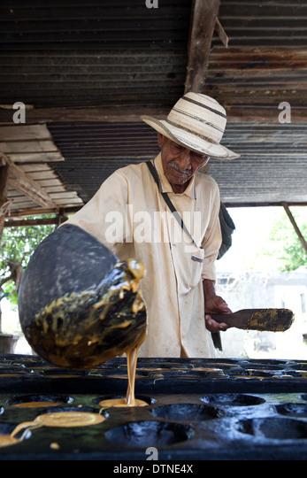 Panamanian man pouring hot juice from sugarcane to make Raspadura, near Penonome, Cocle Province, Republic of Panama. - Stock-Bilder