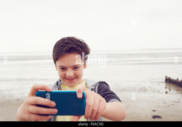 Smiling teenage boy taking smartphone selfie at seaside, Southend on Sea, Essex, UK - Stock Image