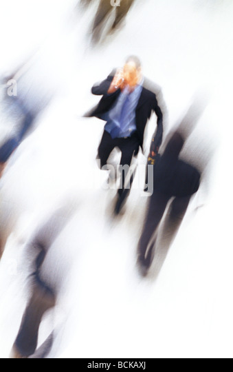 Businessman walking, talking on cell phone, high angle view, blurred - Stock Image