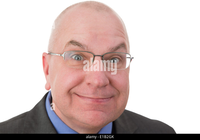 Zealous businessman with a fanatical expression grinning at the camera with his eyes opened wide in expectation - Stock Image