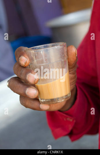 Man holding glass of chai tea, cropped - Stock Image