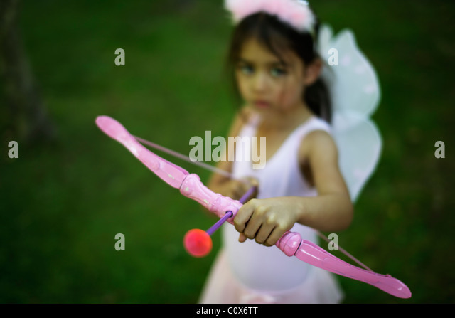 Five year old girl girl in fairy costume with pink bow and arrow - Stock Image