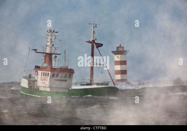 The Netherlands, IJmuiden, Storm. Waves smash against lighthouse or beacon. Ship. - Stock Image