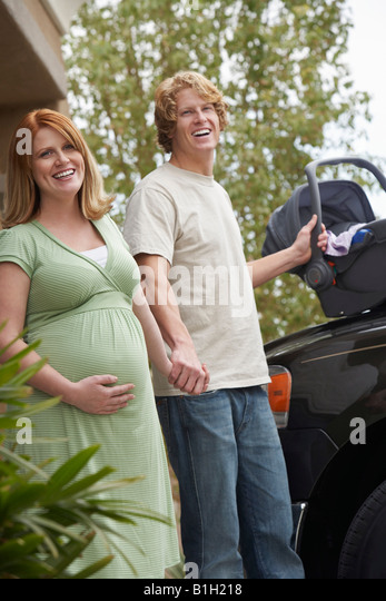 Expectant couple with baby carrier by car, portrait - Stock Image