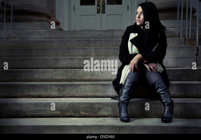 Woman sitting alone on steps waiting - Stock Image
