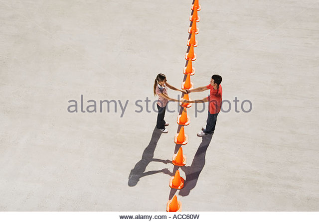 Man and woman holding hands over row of traffic cones - Stock-Bilder