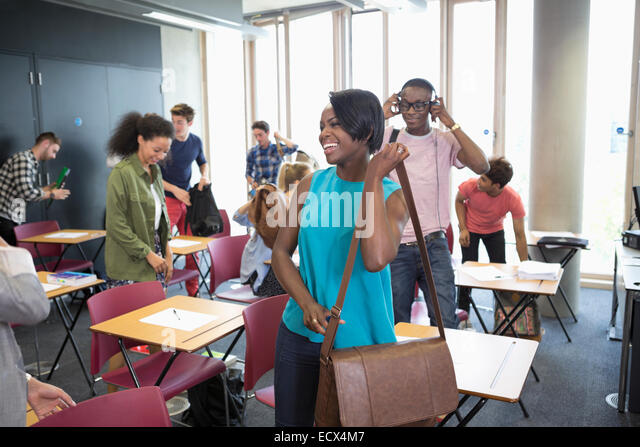 University students packing their bags and leaving classroom - Stock-Bilder