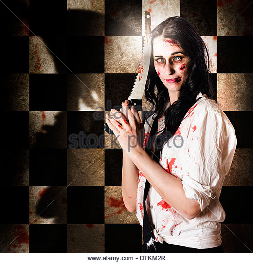 Horror business person covered in blood splatters holding pruning saw in a depiction of slashing prices with cut - Stock Image
