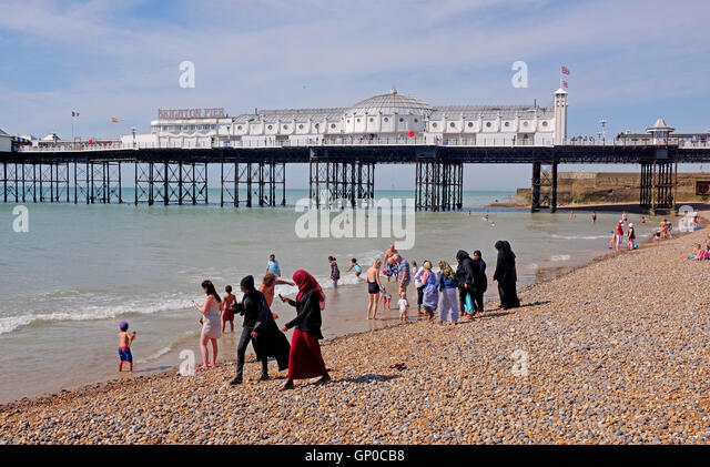 Mix of cultures on Brighton beach with Muslim women and families amongst the crowds enjoying a paddle in the sea - Stock-Bilder